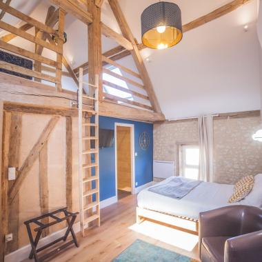 Chambre spacieuse et moderne avec mezzanine en bois et grand lit